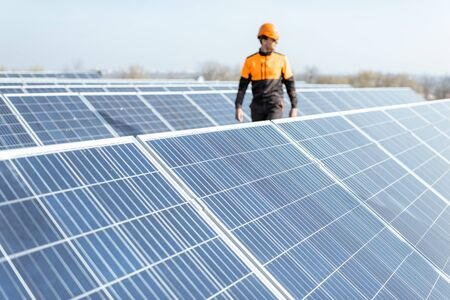 View on the rooftop solar power plant with engineer in protective workwear walking and examining photovoltaic panels. Concept of alternative energy and its maintenance Standard-Bild - 133503653
