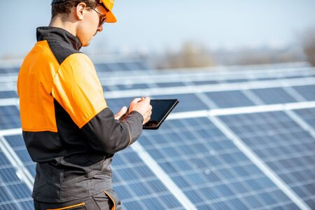 Engineer in protective workwear carrying out service of solar panels with digital tablet on a photovoltaic rooftop plant. Concept of maintenance and setup of solar power station Standard-Bild - 133503654