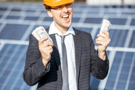 Portrait of an excited businessman with money earned from the electricity production of a solar station. Concept of successful investment in alternative energy Standard-Bild - 133503655