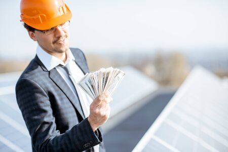 Portrait of a happy businessman with money earned from the electricity production of a solar station. Concept of successful investment in alternative energy Standard-Bild - 133503656
