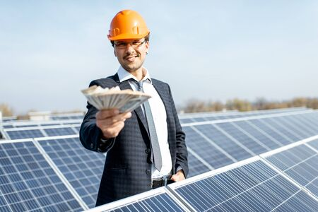 Portrait of a happy businessman with money earned from the electricity production of a solar station. Concept of successful investment in alternative energy Standard-Bild - 133503658