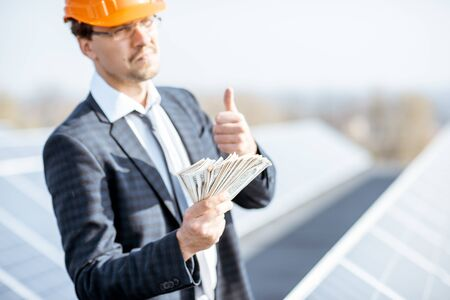 Portrait of a happy businessman with money earned from the electricity production of a solar station. Concept of successful investment in alternative energy Standard-Bild - 133503659