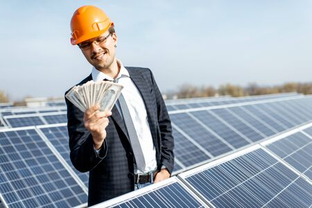Portrait of a happy businessman with money earned from the electricity production of a solar station. Concept of successful investment in alternative energy Standard-Bild - 133503660