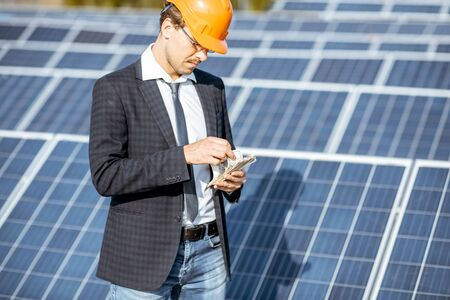 Businessman calculating money earned from the electricity production of a solar station. Concept of successful investment in alternative energy Standard-Bild - 133503662