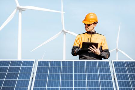 Engineer in protective workwear carrying out service of solar panels with digital tablet on a photovoltaic rooftop plant. Concept of maintenance and setup of solar power station Standard-Bild - 133503671