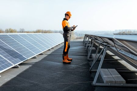 View on the rooftop solar power plant with engineer in protective workwear walking and examining photovoltaic panels. Concept of alternative energy and its maintenance Standard-Bild - 133503667