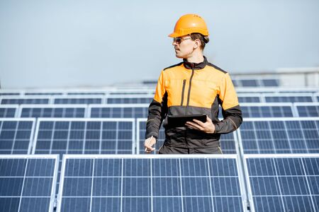 Engineer in protective workwear carrying out service of solar panels with digital tablet on a photovoltaic rooftop plant. Concept of maintenance and setup of solar power station Standard-Bild - 133503668