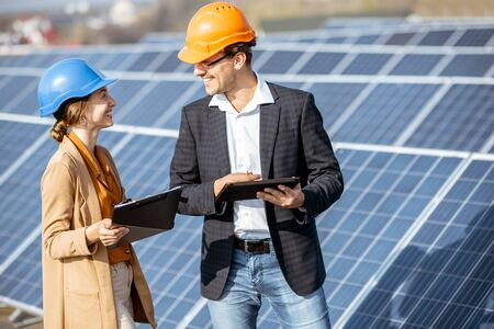 Man and woman dressed in the suits and hard hat as an engineers or business people examining solar station with digital tablet Standard-Bild - 133503672