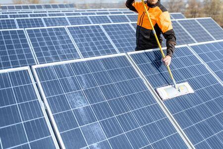 Limpiador profesional en ropa de trabajo protectora limpiando paneles solares con una turba. Concepto de servicio de limpieza de plantas de energía solar