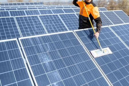 Professional cleaner in protective workwear cleaning solar panels with a mob. Concept of solar power plant cleaning service