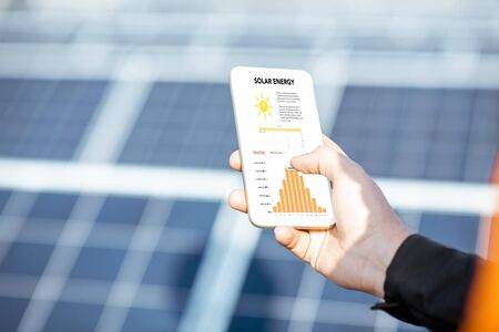 Man examining genaration of solar power plant, holding a smart phone with chart of electricity production. Concept of online monitoring of the electric station