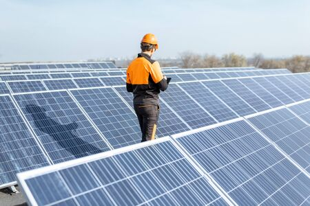 View on the rooftop solar power plant with engineer in protective workwear walking and examining photovoltaic panels. Concept of alternative energy and its maintenance Standard-Bild - 133503677