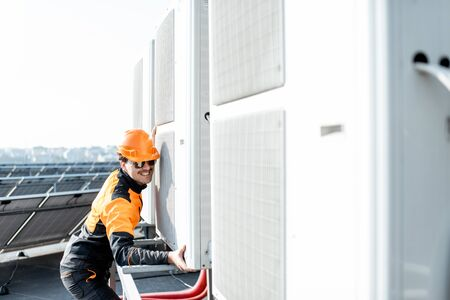 Professional workman in protective clothing installing outdoor unit of the air conditioner or heat pump on the rooftop