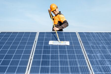 Professional cleaner in protective workwear cleaning solar panels with a mob. Concept of solar power plant cleaning service Standard-Bild - 133503811
