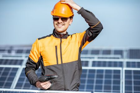 Portrait of a well-equipped worker in protective orange clothing servicing solar panels on a photovoltaic plant. Concept of maintenance and installation of solar stations Standard-Bild - 133503899
