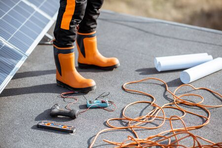 Installing solar panels, close-up on a working tools. wires and man in protective clothing standing on a rooftop with photovoltaic power station Standard-Bild - 133518755