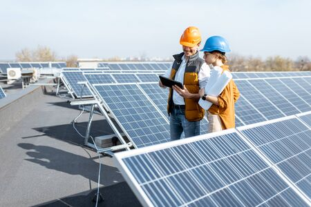Two engineers or architects examining the construction of a solar power plant, walking with digital tablet on a rooftop Reklamní fotografie