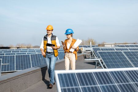 Two engineers or architects examining the construction of a solar power plant, walking with digital tablet on a rooftop Standard-Bild - 133503901
