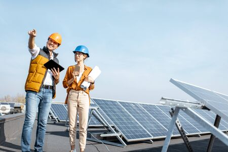 Two engineers or architects examining the construction of a solar power plant, walking with digital tablet on a rooftop Standard-Bild - 133503902