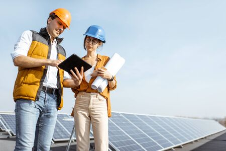 Two engineers or architects examining solar power plant with a digital tablet. Solar station development concept Standard-Bild - 133503903