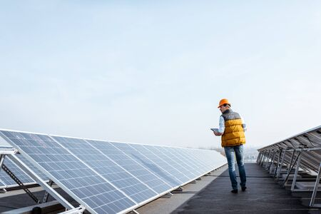 View on the rooftop solar power plant with mann walking and examining photovoltaic panels. Concept of alternative energy and its service Standard-Bild - 133503905