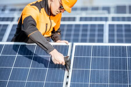 Well-equipped worker in protective orange clothing installing or replacing solar panel on a photovoltaic rooftop plant. Concept of maintenance and installation of solar stations Standard-Bild - 133503928