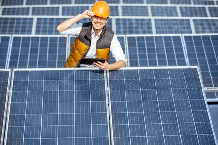 Portrait of a handsome engineer in protective helmet standing with digital tablet on a solar power plant. Solar station development concept Standard-Bild - 133503929