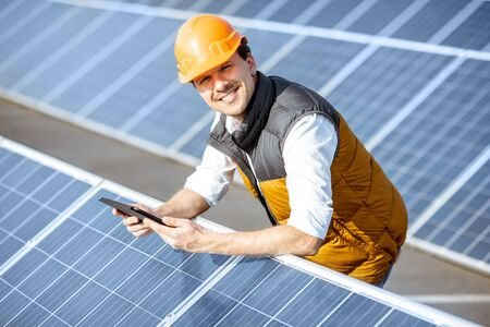 Portrait of a happy engineer in protective helmet standing with digital tablet on a solar power plant. Solar station development concept Standard-Bild - 133503930