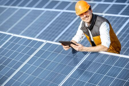 Portrait of a happy engineer in protective helmet standing with digital tablet on a solar power plant. Solar station development concept Standard-Bild - 133503931