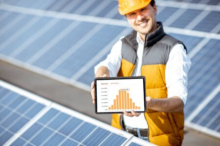Man showing genaration of solar power plant, holding digital tablet with a chart of electricity production. Concept of online monitoring of the electric station Standard-Bild - 133503932