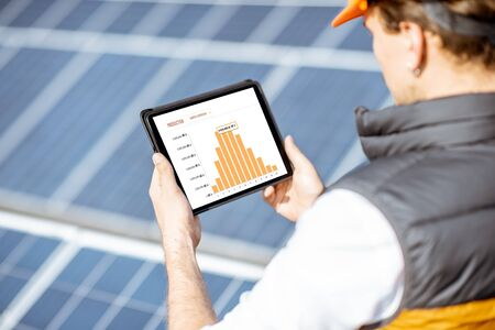 Man examining genaration of solar power plant, holding digital tablet with a chart of electricity production. Concept of online monitoring of the electric station Standard-Bild - 133503933