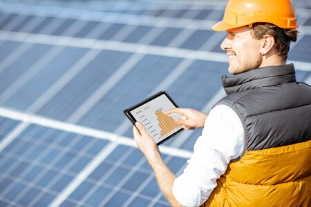 Man examining genaration of solar power plant, holding digital tablet with a chart of electricity production. Concept of online monitoring of the electric station Standard-Bild - 133503935