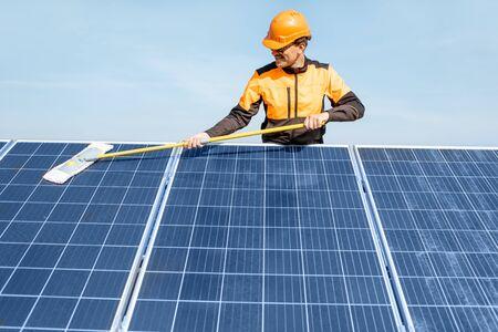 Professioneller Reiniger in Schutzkleidung, der Sonnenkollektoren mit einem Mob reinigt. Konzept des Reinigungsservice für Solarkraftwerke