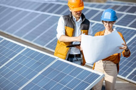 Two engineers or architects examining the construction of a solar power plant, standing with blueprints between rows of solar panels Imagens