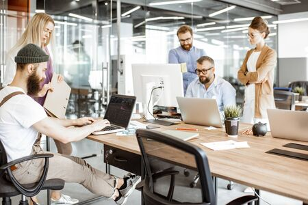 Group of diverse colleagues working on the computers in the modern office or coworking space, bearded hipster as a programmer writing code