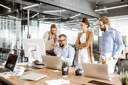 Senior manager having a meeting with office workers standing together near the working place in the modern office. Concept of a small conference and teamwork