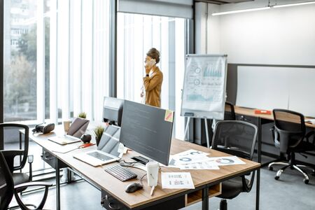 Young business woman talking on the phone while standing near the window in the modern office with computers on the foreground 写真素材