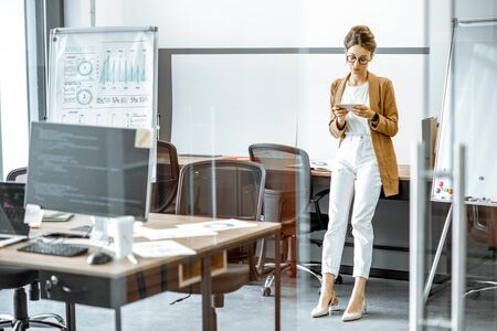 Young business woman preparing for a presentation, standing alone with phone near flipchart in the modern office or coworking space