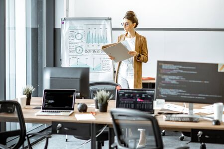 Young business woman preparing for a presentation, standing alone with documents near flipchart in the modern office or coworking space 写真素材
