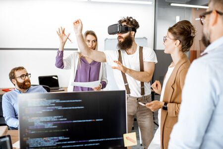 Group of diverse colleagues during small conference in the office, creative bearded man trying a new product with virtual reality goggles