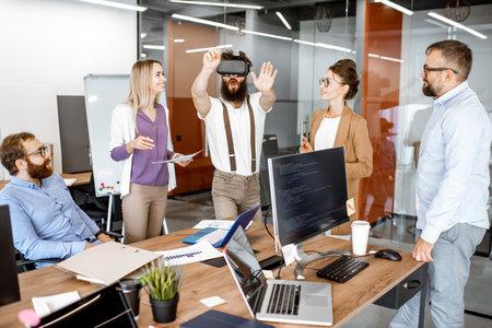Gruppo di diversi colleghi durante una piccola conferenza in ufficio, uomo barbuto creativo che prova un nuovo prodotto con occhiali per realtà virtuale