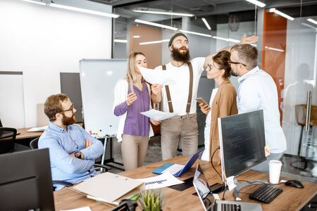 Group of diverse colleagues meeting in the office, creative bearded hipster telling emotionally a new idea. Teamwork concept