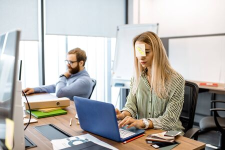 Young woman with work reminder sticker on her head feeling tired during the hard work with coworkers in the office 写真素材