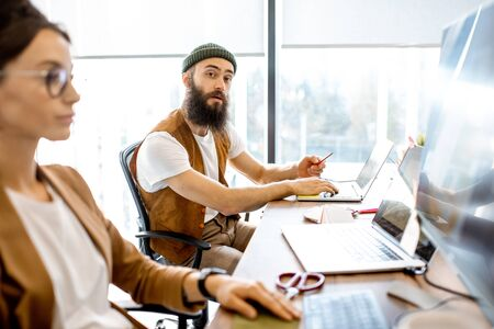 Creative young man and woman as a web designers working on the computers in the office or coworking space