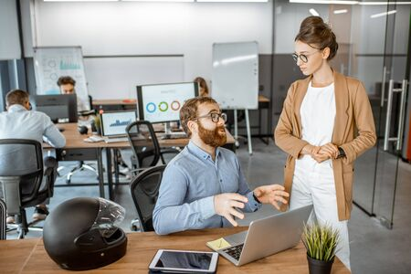 Two young colleagues talking at the working place, solving some working moments in the busy office or coworking space