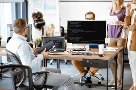 Group of diverse colleagues working with computers in the modern office or coworking space, writing programming code and working with vr goggles
