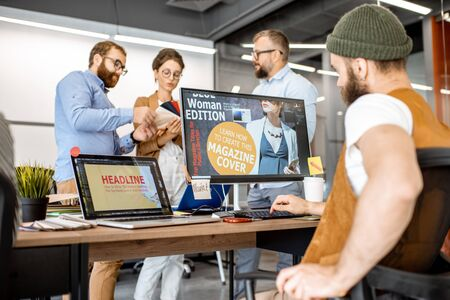 Group of diverse creative people working as a web designers in the modern office, bearded hipster designing cover on the computer