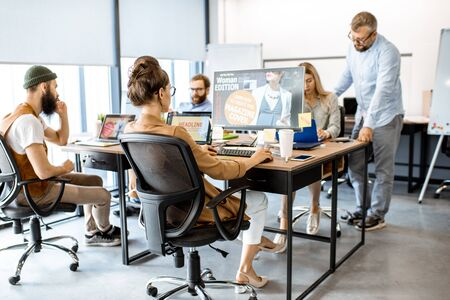 Group of diverse and creative colleagues working on computers in the modern office or coworking space, working on web design