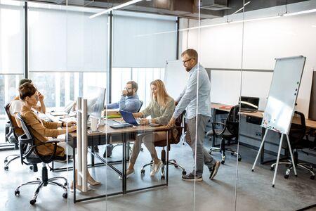 Gruppe verschiedener Kollegen, die an den Computern im modernen Büro oder Coworking Space arbeiten, weite Innenansicht Standard-Bild