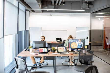 Modern office room of web designers with working places and people working